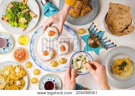 Festive feast on Hanukkah, table setting, hands over table horizontal
