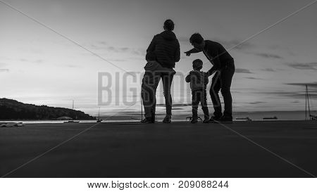Greyscale image of parents with their young children silhouetted against a sunset sky at the coast as the man points it out to one child.