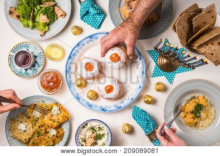 Jewish religious holiday Hanukkah, feast, hands over the table horizontal