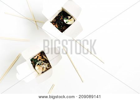 Noodles in box and chopsticks on white background. Flat lay top view. Chinese takeaway food concept.