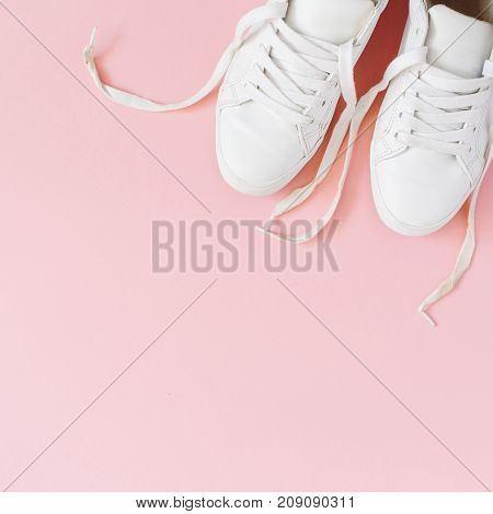 Fashion blog look. White women's sneakers on pink background. Flat lay top view beauty female background.