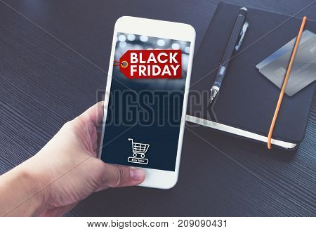Black Friday Sale Tag With Shopping Cart On Mobile Screen,hand Holding Smart Phone Over Black Book A