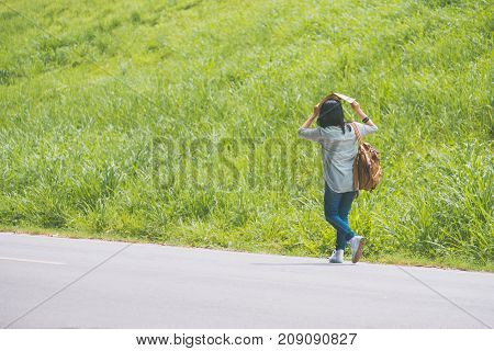 Asian traveler with backpack walking on country road and use map for protect sunshine and looking forward to see direction near green grass in sunny dayAlone travel or single traveler concept