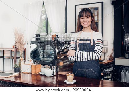 Asian female barista wear jean apron crossed her arms at counter bar with smile facecafe service conceptowner business start up