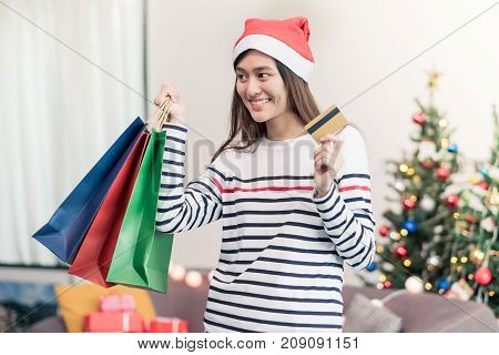 Happy Asia woman use credit card buy Christmas gift in shopping bag at home in partyHoliday online shopping