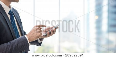 Business man using smart phone on window with city building background and copy space.