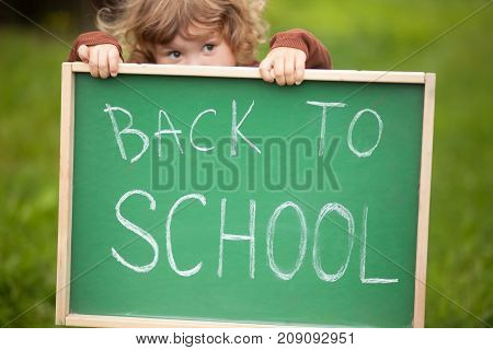 Cute Toddler Girl Hiding Behind A Back To School Blackboard