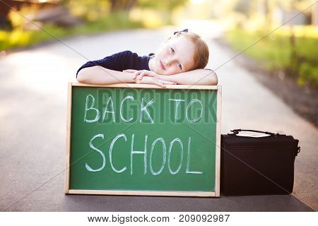 Adorable little blond 8-10 years old school girl ready for back to school wearing school uniform holding school bag and back to school chalkboard.