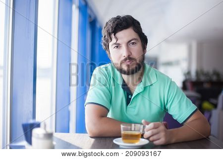 Handsome young man at the restaurant drinking tea sitting near the window.