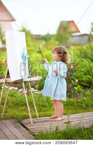Adorable little painter. Cute toddler girl painting on the easel in the garden and having fun. Talented kids. Early art education.