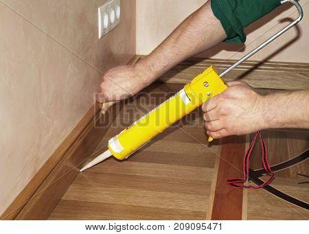 Repairman Installing Skirting Board Oak Wooden Floor with Caulking Gun Glue from Cartridge. Flooring with Wooden Batten Repair.