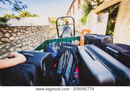 Family riding a tractor trailer with suitcases and luggage. Family on vacation is using transport or transfer from airport or a port to selected apartment or a hotel. Small tractor is pulling a trailer with tourists and baggage.