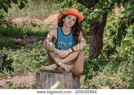 Portrait of nice girl in cowboy hat. Enviable young woman sits on a stump the backdrop of the garden.