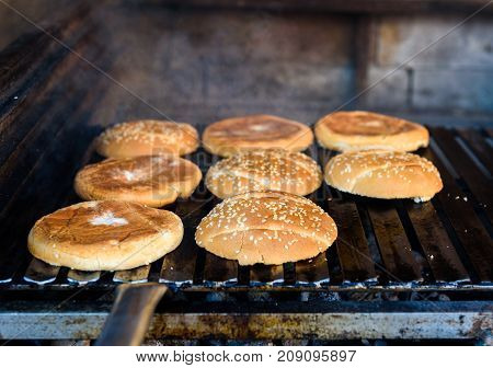 Making and grilling hamburger buns with sesame on coal grill. Preparing roasted food on barbecue BBQ grill in outdoor fireplace and u-shape fire grid. Last step of making delicious burgers.