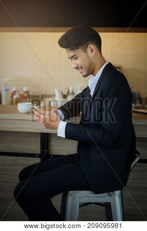 Happy smart businessman playing smartphone to check good business project news with cup of coffee at cafeteria. Smile handsome Asian 30s man work at Coffee shop by using 4g mobile data technology.