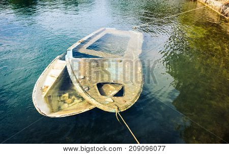Sunken wooden boat in sea or lake tied to shore. Small plastic boat with broken top is submerged int he sea while still tied to shore and pier with ropes. Silba Croatia.
