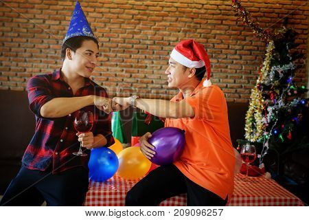 Happy Gay men couple with santa hats looking each other and touching hands to celebrate Christmas party. Xmas celebration with wine or champagne drink Colorful balloons X'mas tree.