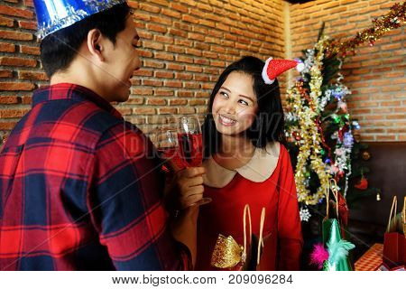 Happy Asian couple 20 to 30 years old with santa hats holding hands with glasses of red champagne to celebrate christmas or xmas and new year party.