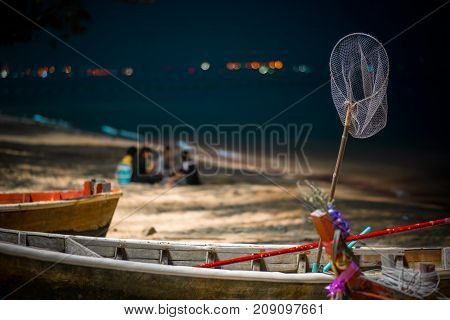 Thai fishing boat with tackle stands on the shore amid vacationers fishermen on the beach