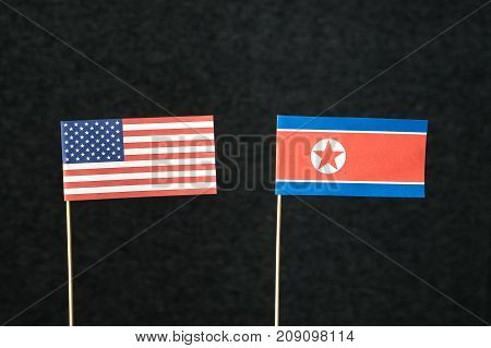 The flag of United States of America (USA) and North Korea made from paper on wooden stick against dark background.