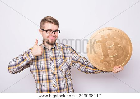 Happy cheerful young businessman holding big golden bitcoin on white background. Crypto currency, virtual money, internet and economics concept.