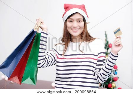 Young cute asian woman wearing Christmas hat smiling while holding shopping bags and credit card Christmas shopping concept
