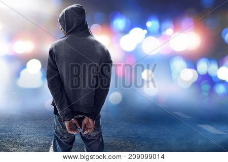Unknown hacker in handcuffs on the street