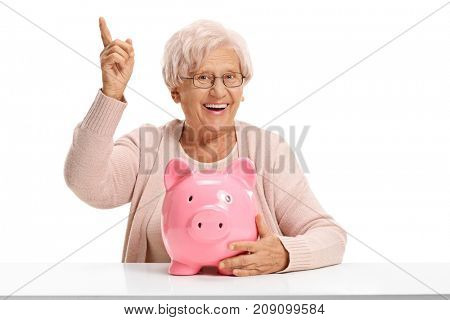 Joyful elderly woman with a piggybank seated at a table pointing up isolated on white background