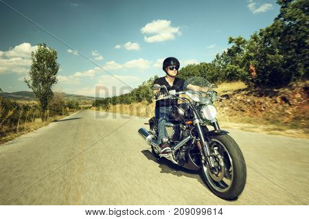 Biker riding a motorcycle on an open road