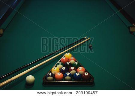 Playing billiard. Billiards balls and cue on green billiards table. Billiard sport concept. Pool billiard game.