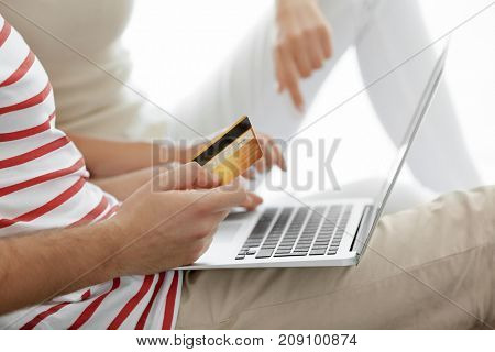 Couple with laptop and credit card on light background. Internet shopping concept