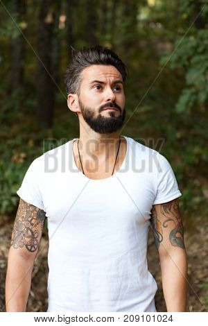 Young handsome bearded hipster man in the field