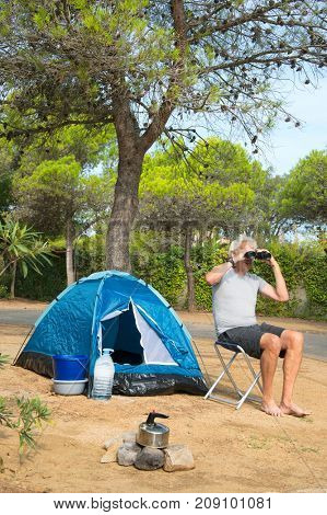 Man at camping with spyglass alone with blue dome tent for adventure