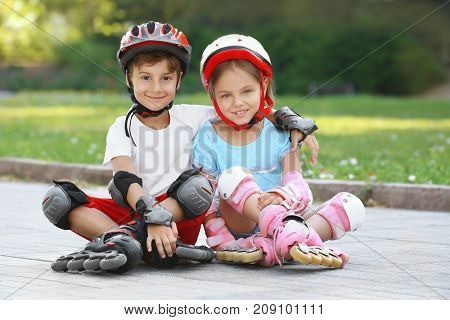 Cheerful boy and girl on roller skates sitting in park