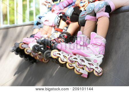 Legs of children on rollers at skate park