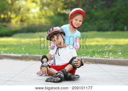 Cheerful boy and girl on roller skates in park