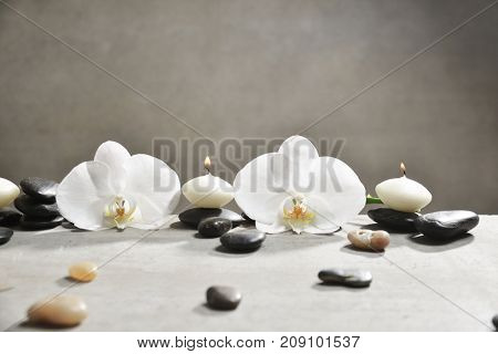 Two white orchid with pile of gray stones and candle on gray background