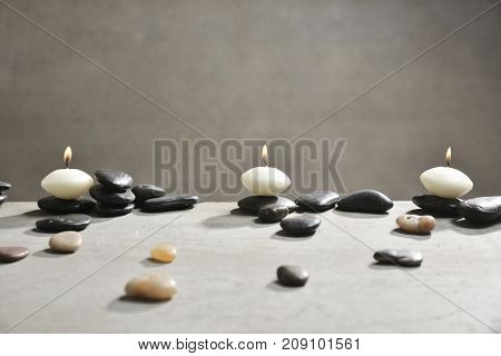 White stones and black stones with three candle on gray background