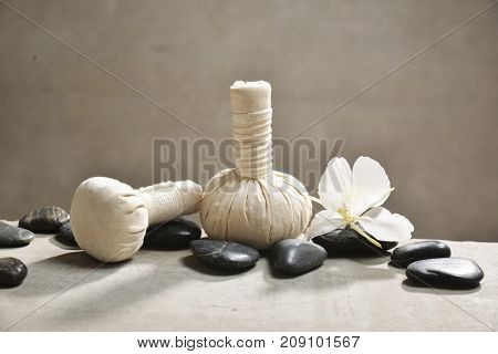 white orchid with pile of black stones and, herbal ball ,on gray background