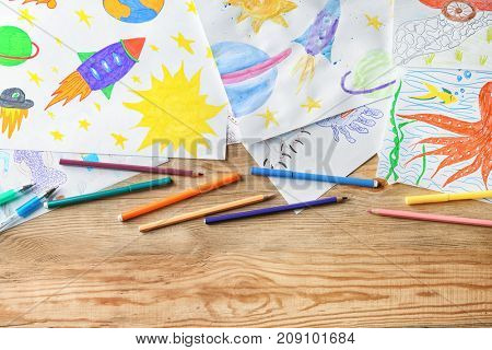 Children's drawings on wooden background