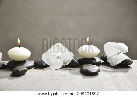 hydrangea petals with pile of black stones and white candle on gray background
