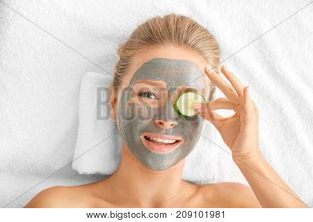Young woman with facial mask and cucumber slice in spa salon