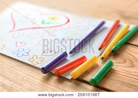 Child's drawing with flowers and hearts on wooden table, closeup
