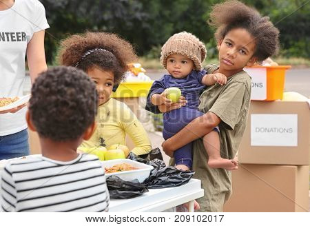 Volunteer sharing food with poor African children outdoors