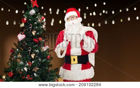 christmas, holidays, gesture and people concept - man in costume of santa claus with bag and christmas tree showing thumbs up over garland lights background