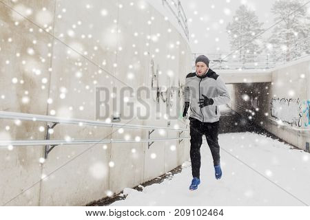 fitness, sport, people, season and healthy lifestyle concept - young man running out of pedestrian subway tunnel in winter