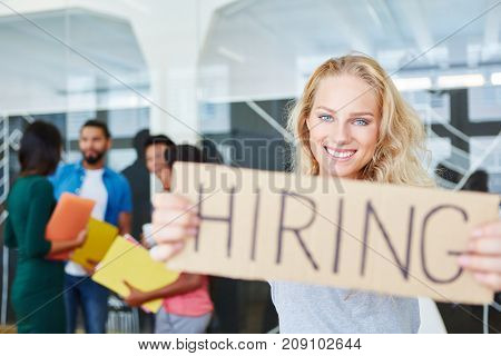 Woman in start-up holding sign as hiring advertising