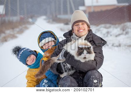 boys plays with a cat outdoors in winter