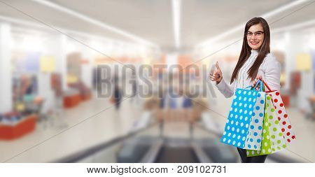 A woman is a buyer with a package of gifts on the background of a market, a shopping center.