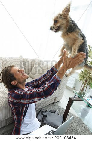 modern young man playing with his dog in a spacious living room